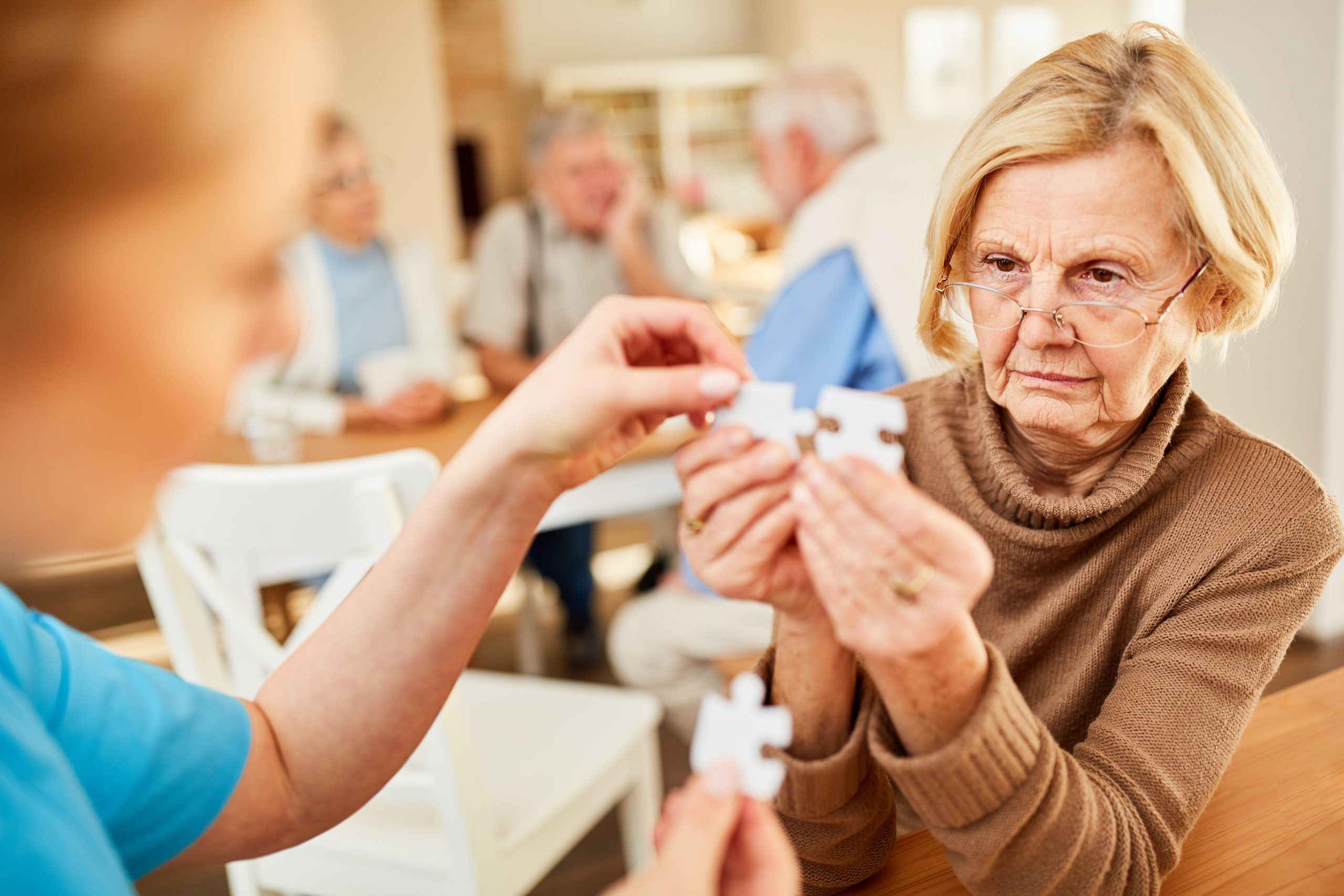 Senior with Alzheimer's or dementia has difficulty with puzzle pieces.